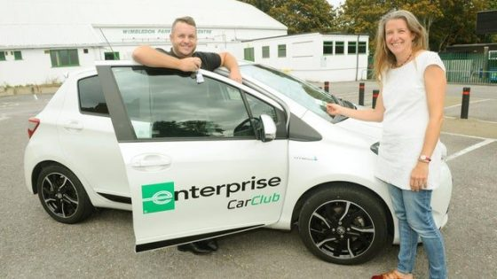 A man and woman standing next to a white compact hatchback car belonging to Portsmouth Enterprise Car Club.