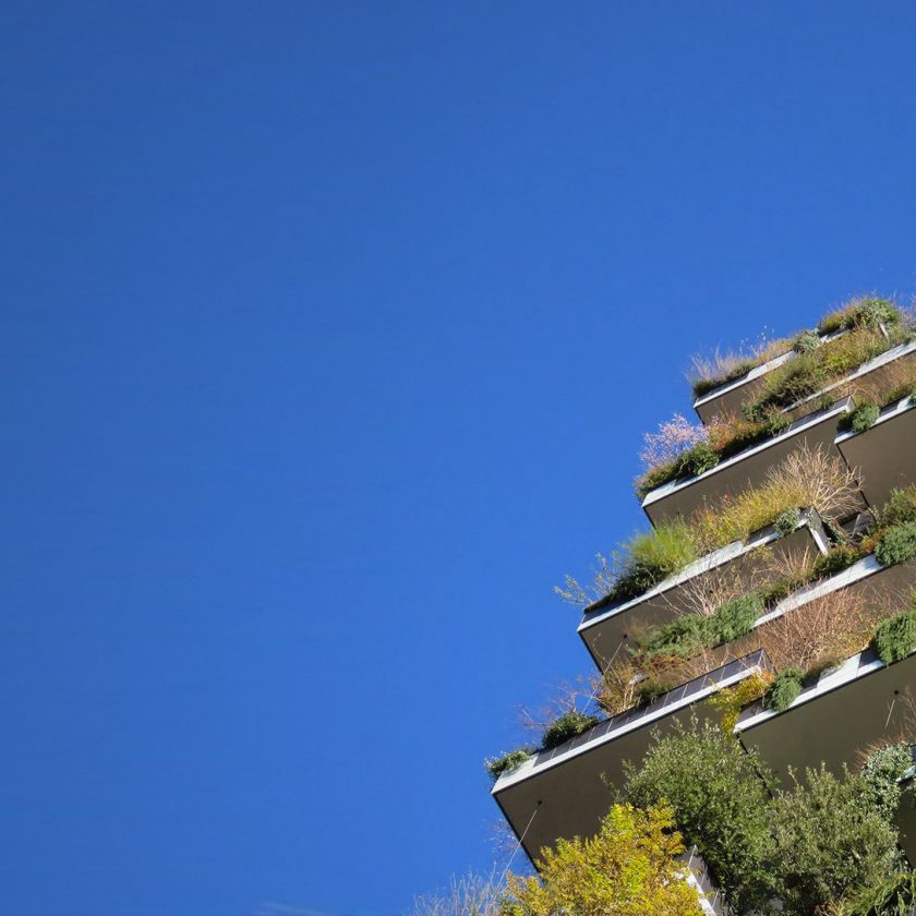 Looking up at a 'vertical forest' tower block design by Stefano Boeri, against a blue sky.