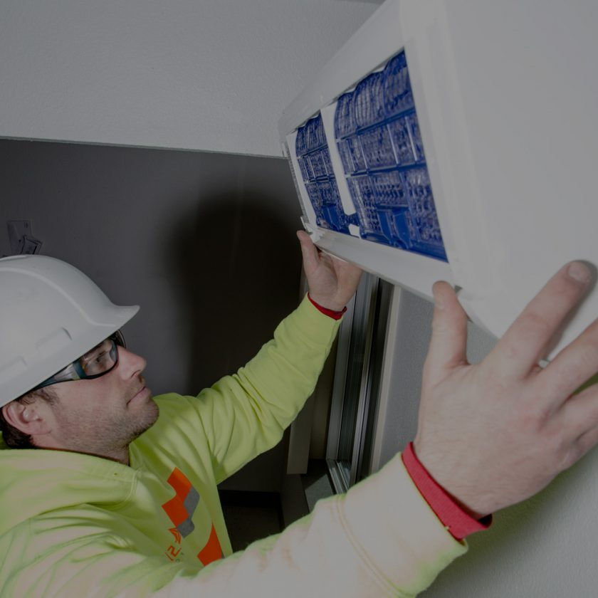 A heating engineer installs a heating system panel on a wall.